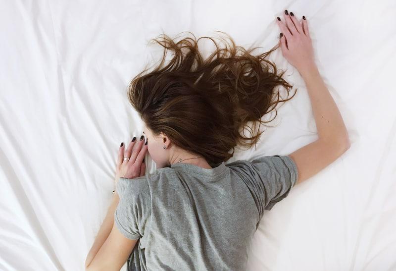 Auf dem Bett liegt ein junges Mädchen in einem kurzärmeligen T-Shirt