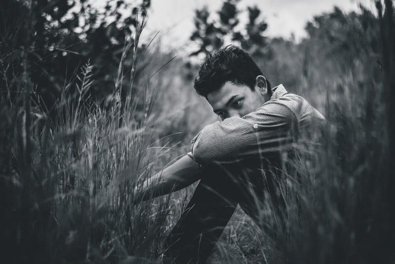 Der Mann sitzt alleine im Gras und denkt nach