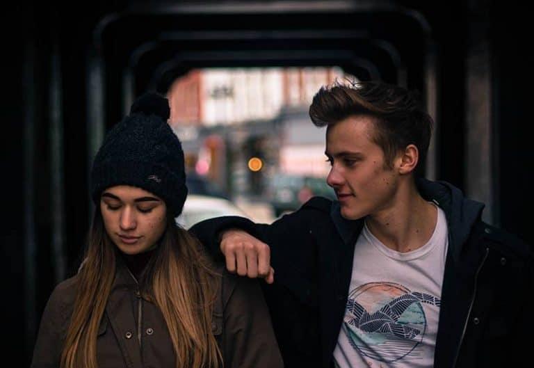 Der junge Mann hält das Mädchen an der Schulter
