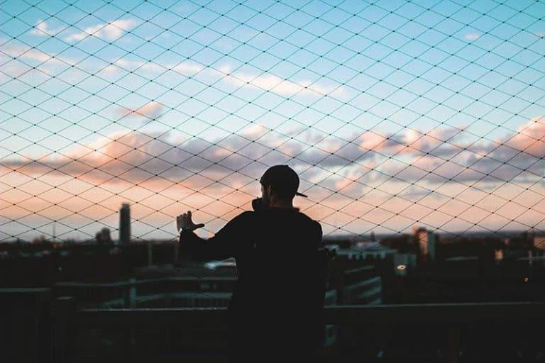 Der junge Mann steht vor einem hohen Zaun