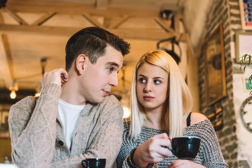 Die Blondine und der Mann sitzen in einem Café und unterhalten sich