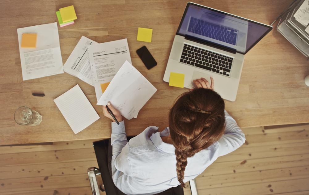 Die Frau am Tisch arbeitet an einem Laptop