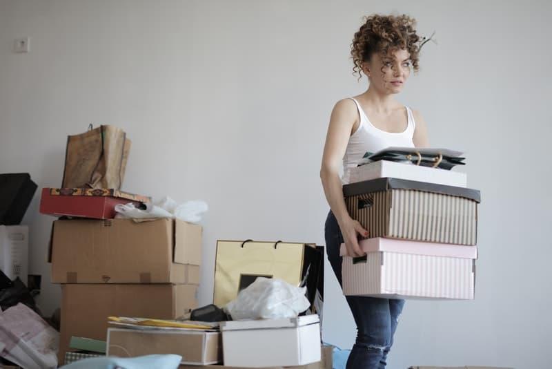 Die Frau trägt eine Schachtel mit einigen Dingen