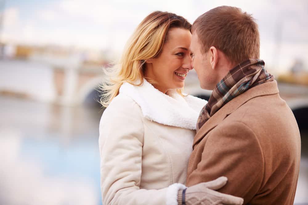 Draußen in einer Umarmung stehen eine lächelnde Blondine in einem weißen Pelzmantel und ein Mann in einem braunen Mantel