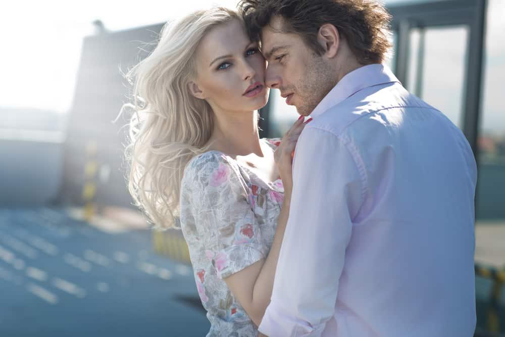 Draußen steht eine Blondine in den Armen eines Mannes in einem weißen Hemd