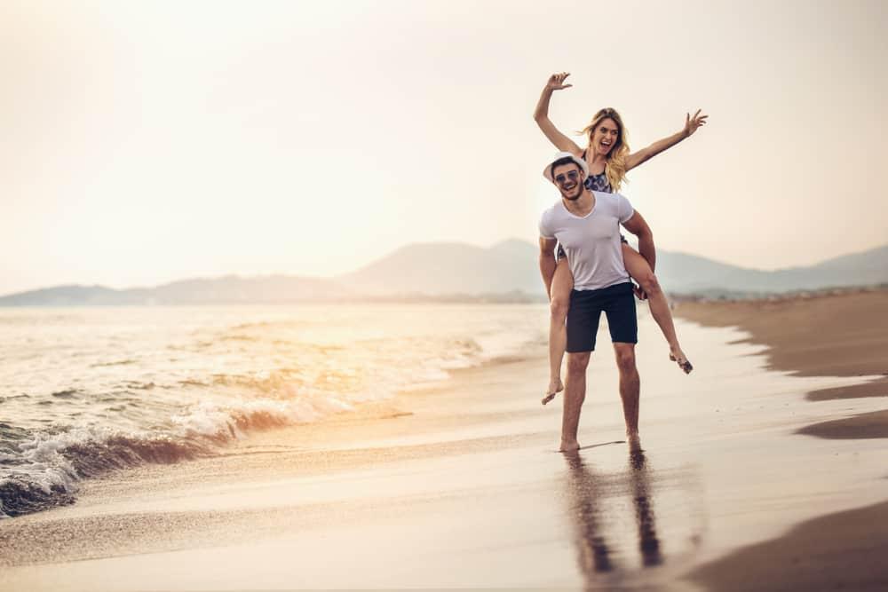 Ein Mann in Sonnenschirmen am Strand trägt seine Frau auf dem Rücken