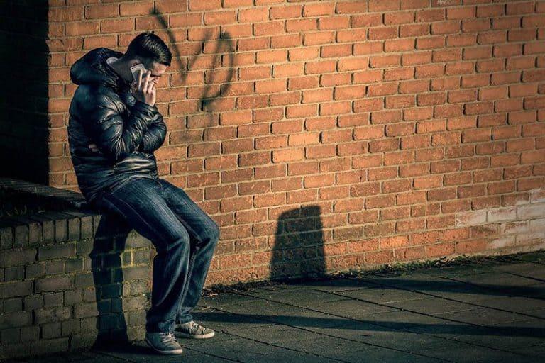 Ein Mann sitzt auf Beton und telefoniert
