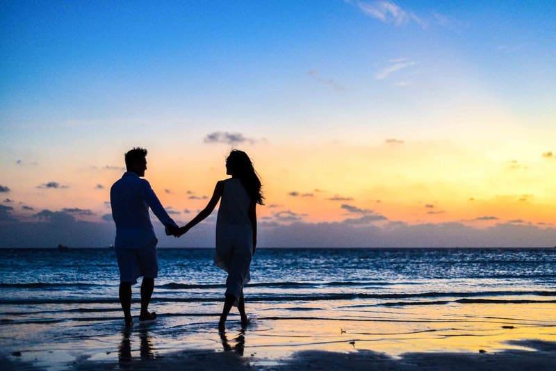 Ein Mann und eine Frau gehen bei Sonnenuntergang barfuß am Strand spazieren