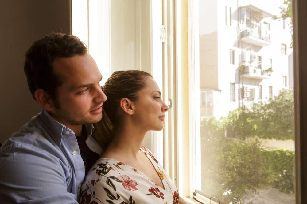 Ein liebevolles Paar in einer Umarmung steht auf und schaut aus dem Fenster
