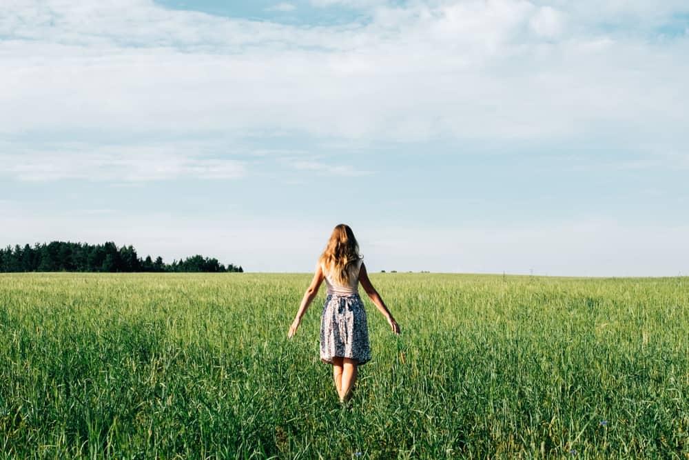 Eine Blondine in einem Rock geht durch das Gras