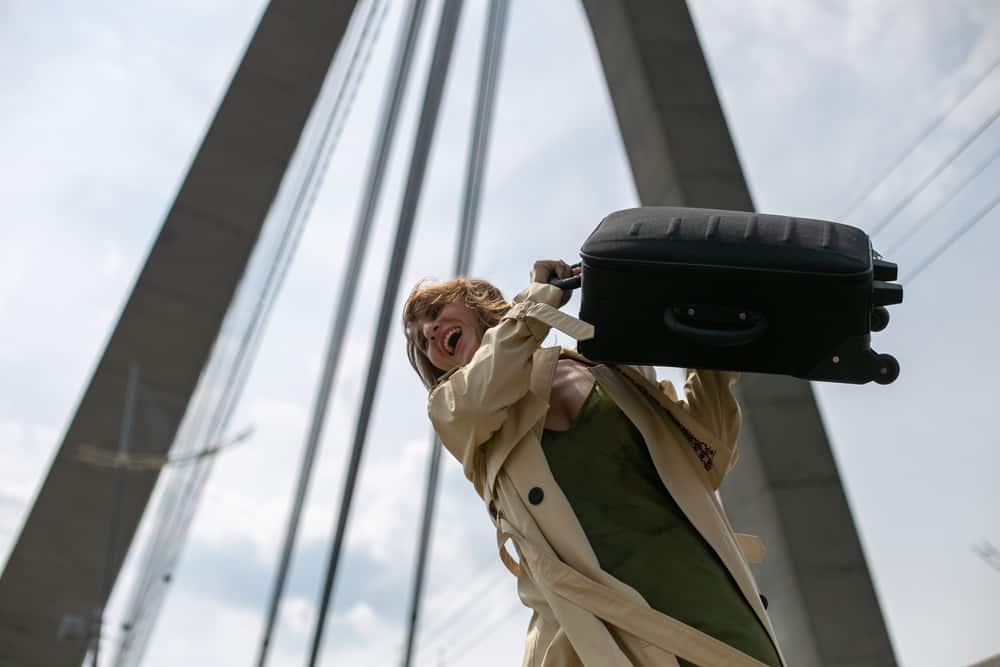 Eine Frau im Mantel wirft einen Koffer von der Brücke
