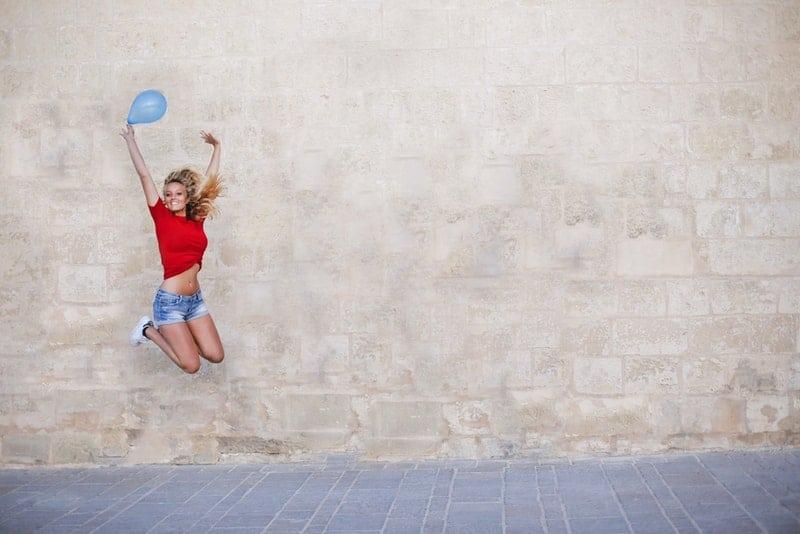 Eine Frau in kurzen Hosen mit einem Ballon in einem Fluss springt