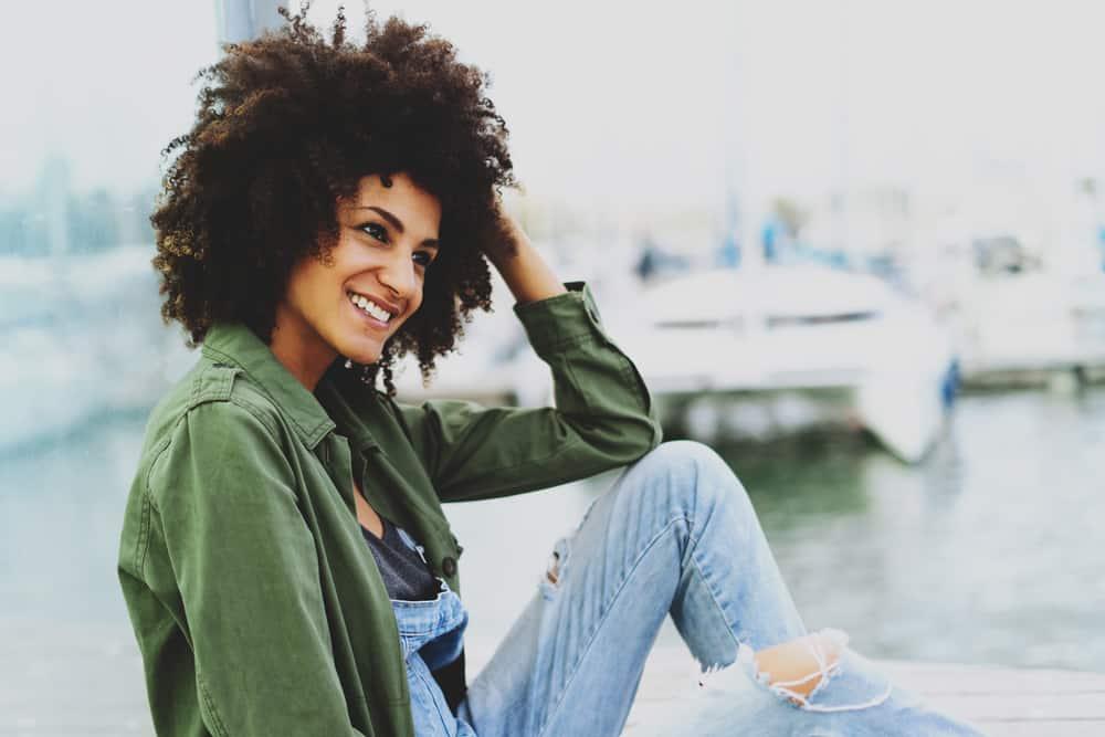 Eine Frau mit einer Afro-Frisur sitzt auf dem Dock