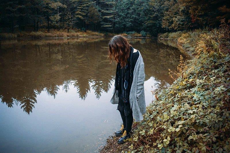 Eine Frau mit gesenktem Kopf steht am Ufer des Sees