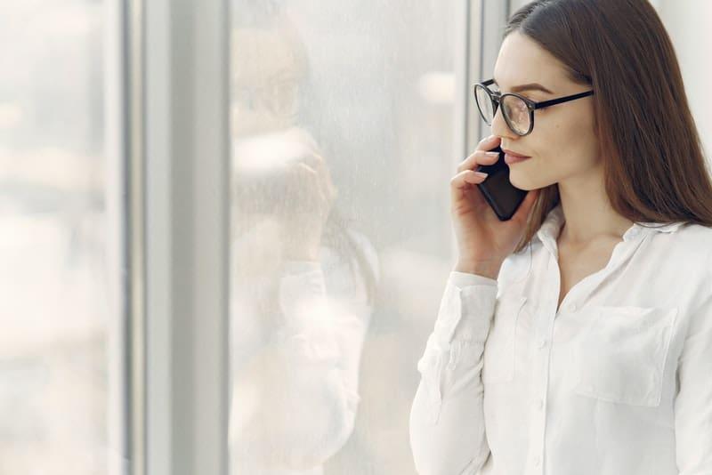 Eine besorgte Frau am Fenster steht auf und ruft jemanden auf ihrem Handy an