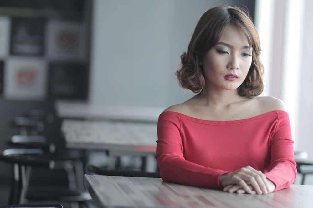 Eine traurige Frau in einem rosa T-Shirt sitzt in einem Café