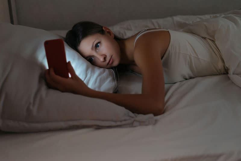 Frau, die auf weißem Kissen liegt und auf ihr Telefon schaut