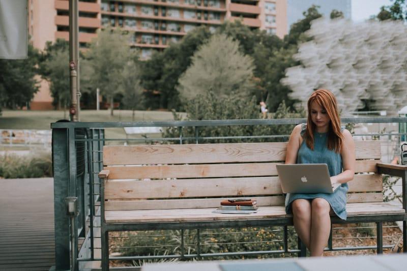 Frau sitzt auf Bank weiß mit MacBook Pro