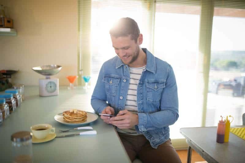 Junger Mann, der Handy im Restaurant benutzt