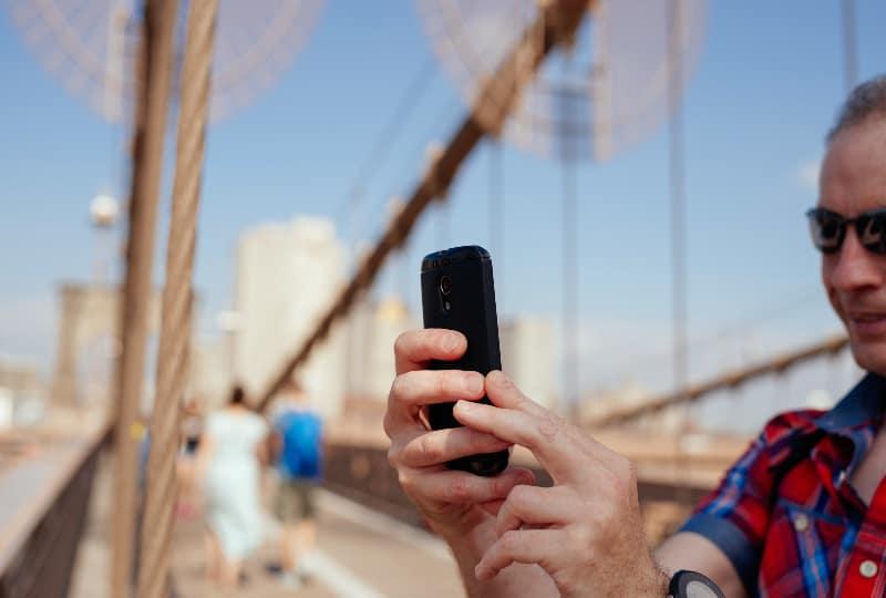 Mann auf der Brücke macht ein Selfie
