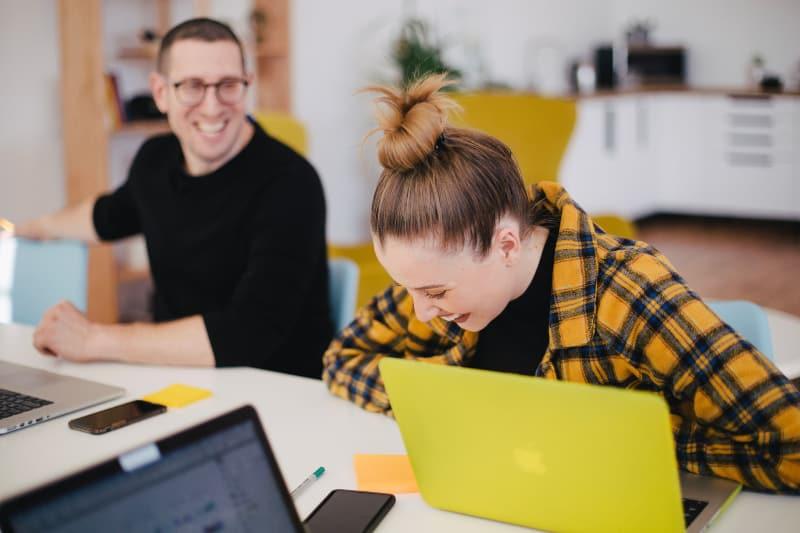Mann und Frau lachen, während sie vor Laptops sitzen