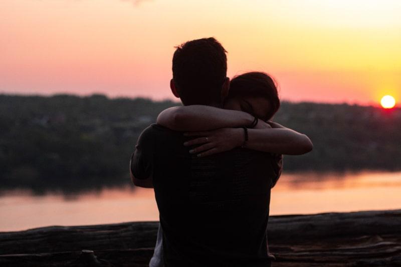 Paar umarmt sich während des Sonnenuntergangs