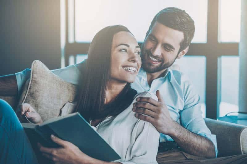 Schönes junges liebendes Paar, das aneinander bindet und lächelt, während Frau ein Buch hält
