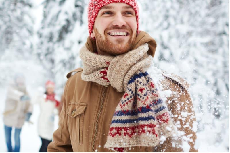 Draußen im Schnee steht ein lächelnder Mann mit einem Schal und einer Wintermütze