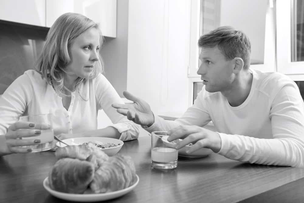 ein liebevolles Paar, das beim Frühstück ernsthaft redet