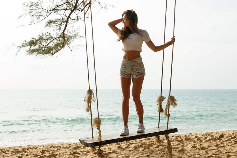 eine Frau, die auf einer Schaukel am Strand steht