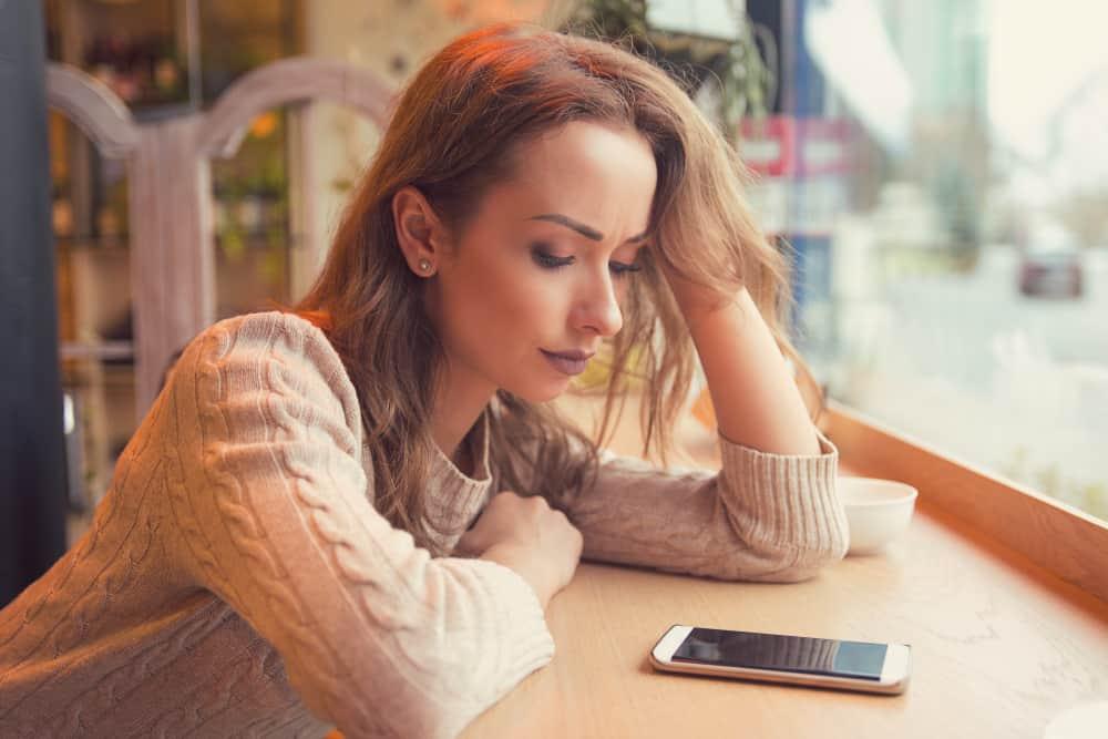eine Frau, die in einem Café sitzt und traurig auf ihr Handy schaut