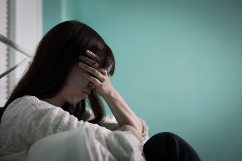 eine Frau, die sich deprimiert fühlt und auf dem Bett sitzt