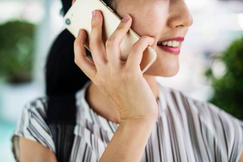 eine Frau mit einem Lächeln im Gesicht, die auf einem Handy spricht