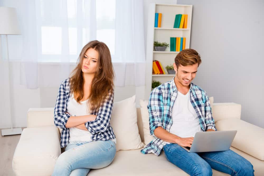 eine traurige Frau, die auf der Couch neben einem lächelnden Mann sitzt, der einen Laptop benutzt