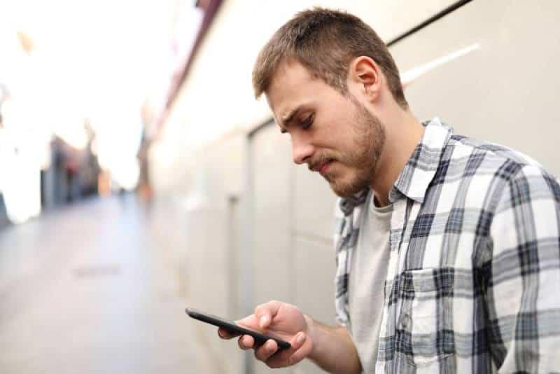 unglücklicher Mann, der auf seinem Telefon eine SMS schreibt