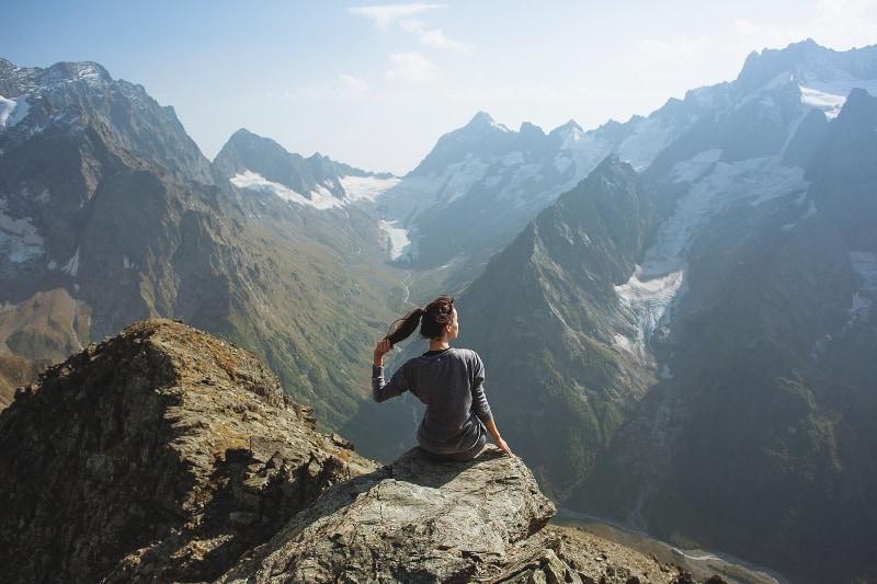 Ein glückliches Mädchen sitzt am Rande eines Berges