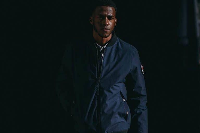 Ein schwarzer Mann in einer Jacke geht