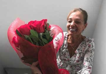 eine ältere Frau mit Rosen in der Hand