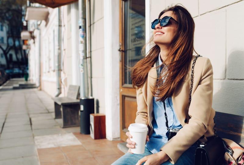 Ein junges lächelndes Mädchen in einem Mantel sitzt auf einer Bank