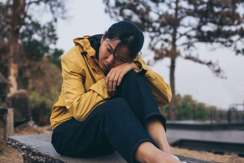 Eine asiatische Frau in einer gelben Jacke sitzt traurig auf einer Bank