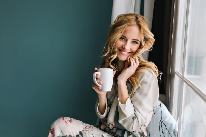 Eine entzückte Blondine sitzt am Fenster und trinkt Tee