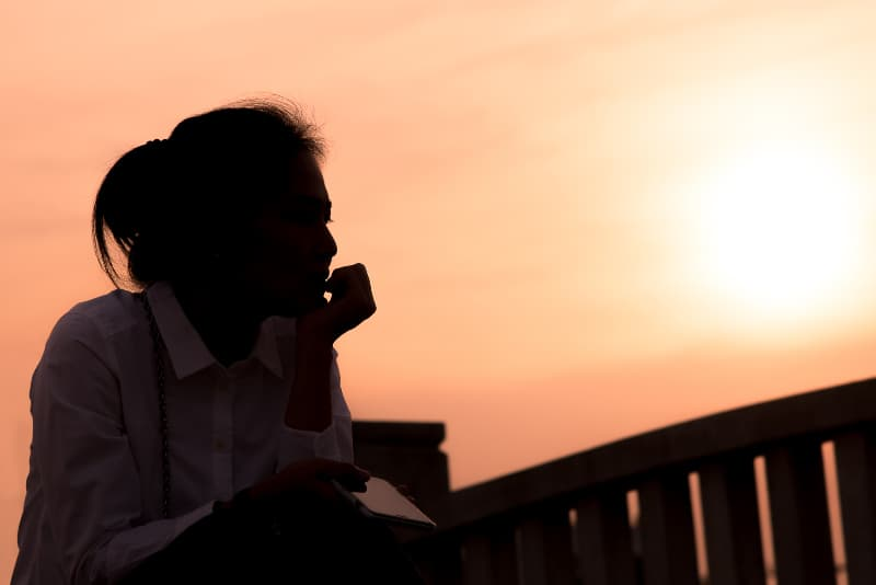 Eine traurige Frau sitzt allein während des Sonnenuntergangs