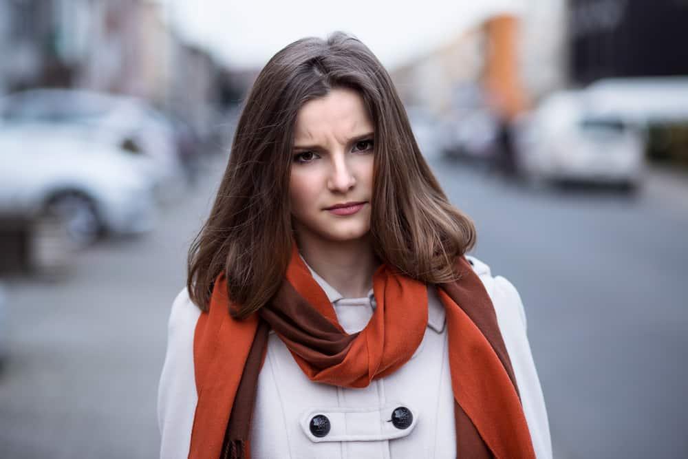 Eine unglückliche Frau mit einem Schal um den Hals geht die Straße entlang