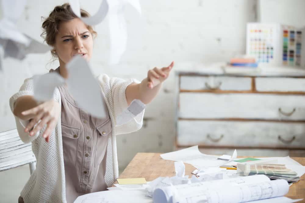Eine wütende Frau wirft Papiere um das Haus