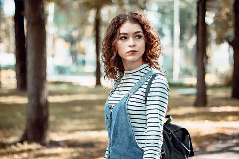 Frau mit den lockigen Haaren, die im Park stehen