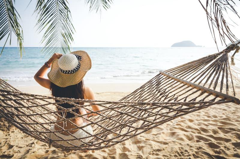 Frau sitzt auf Schaukel am Strand