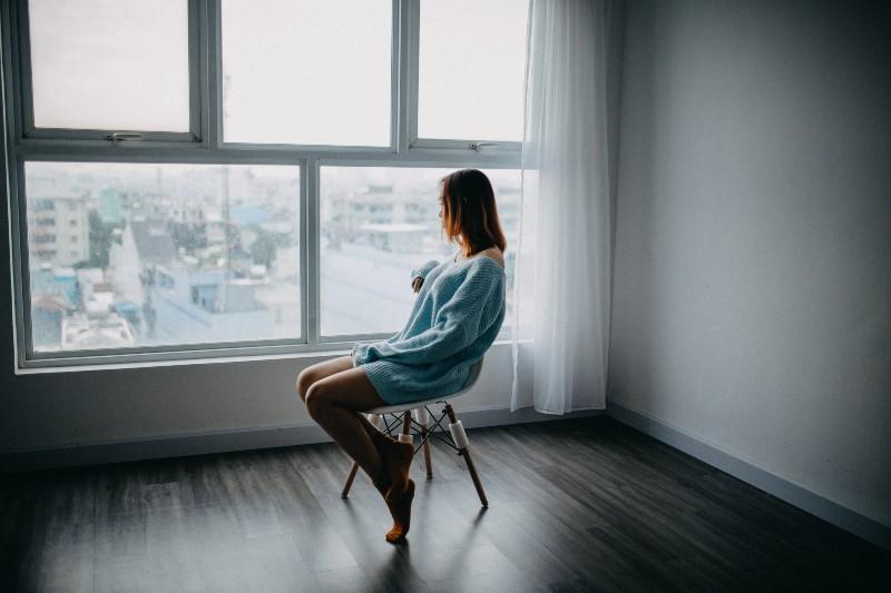 Frau sitzt auf braunem Stuhl