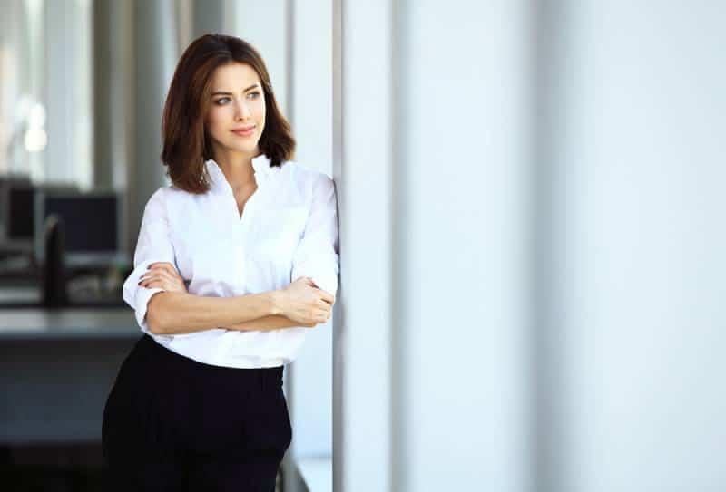 Geschäftsfrau im weißen Hemd mit verschränkten Armen, die neben Fenster stehen
