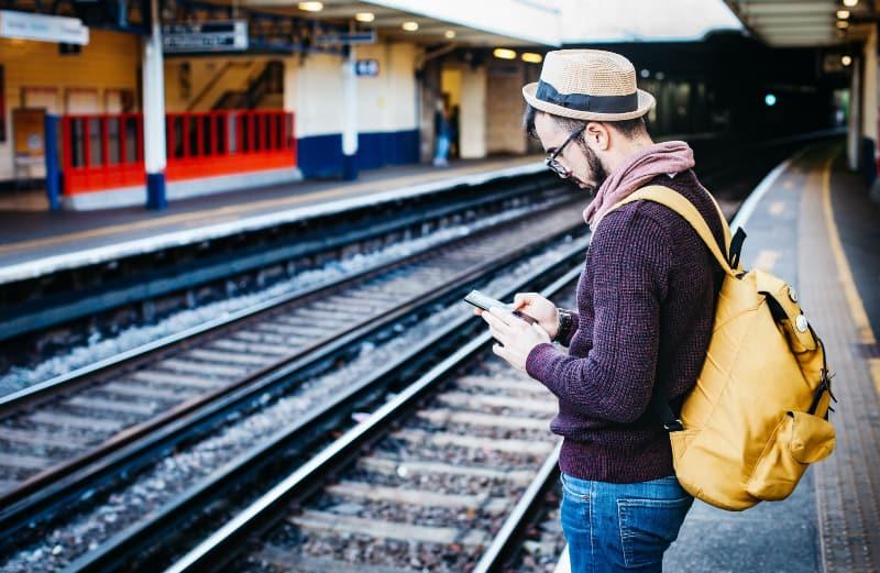 Mann, der Telefon benutzt, während er vor Zug steht
