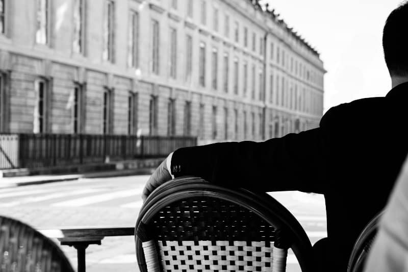 Mann in schwarzer Anzugjacke sitzt im Straßencafé